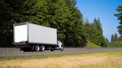 dry van box trailer on the green highway road