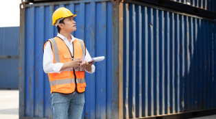engineer writing on clipboard in containers warehouse storage