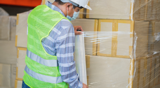 worker wearing protective face mask and safety suite wrapping stretch film parcel on pallet in warehouse