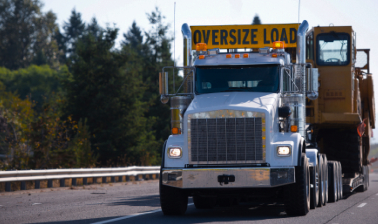 """Semi-truck with """"oversize load"""" sign  transporting large oversized digger."""