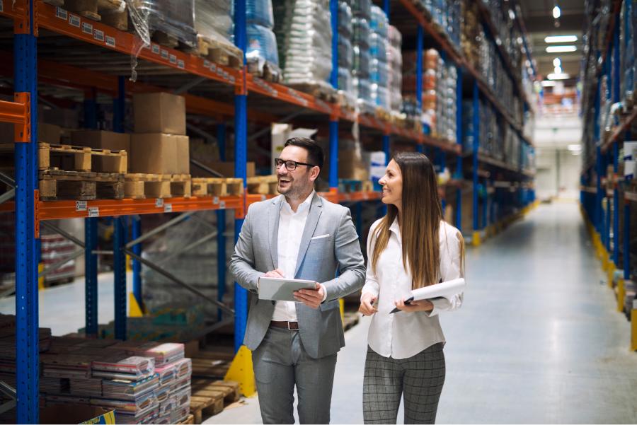 Two people walking through large warehouse center.