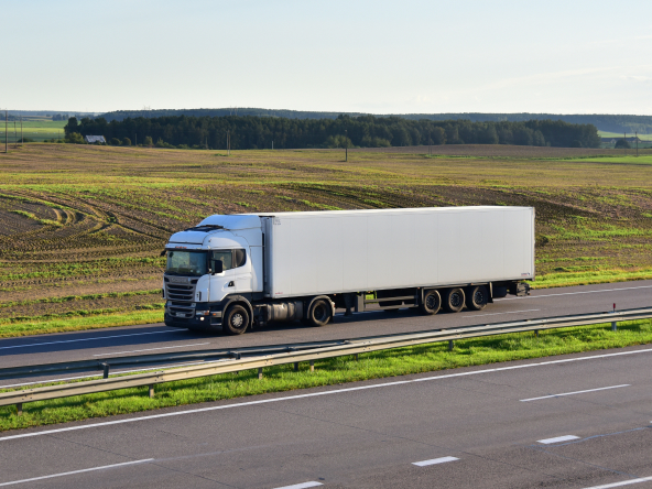 Semi-trailer truck driving along highway on blue sky background.
