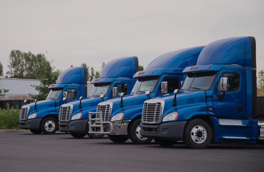Side view of the blue big rigs semi trucks tractors