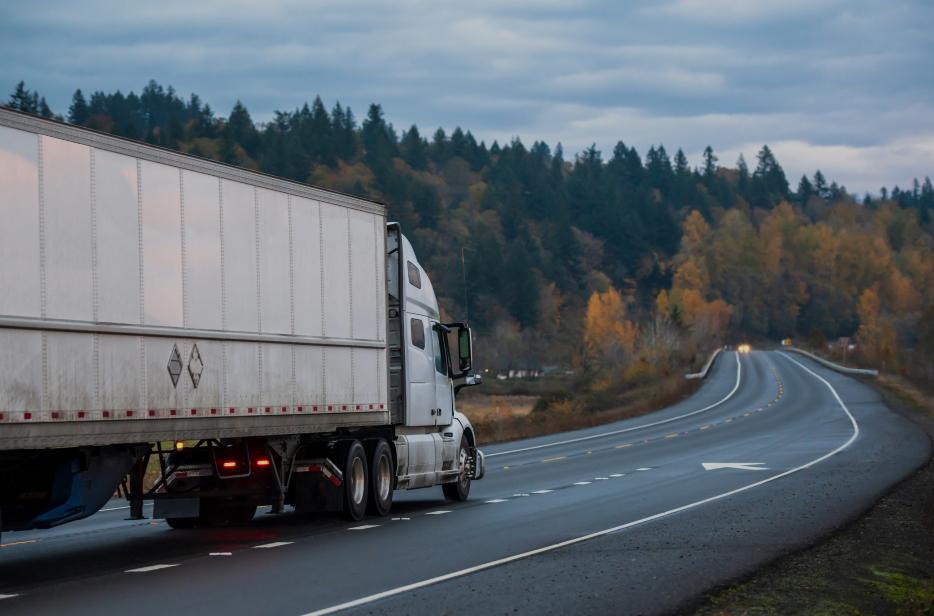 Big rig white long haul semi truck with semi trailer running