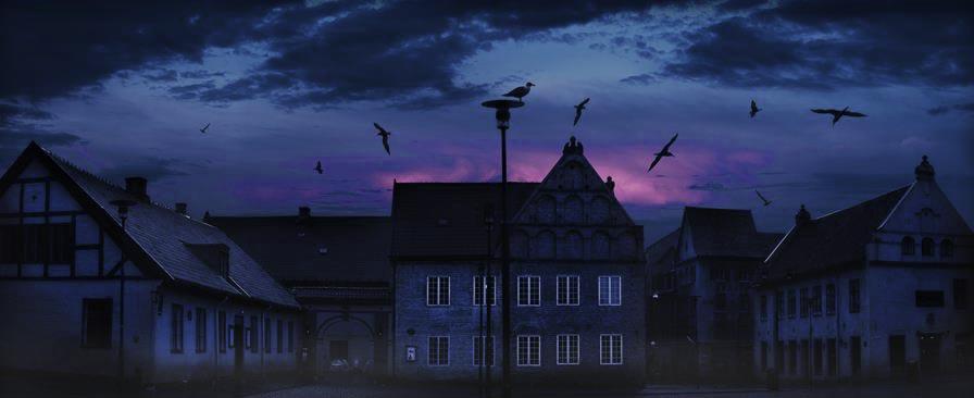 Et kveldsbilde av Christiania Torv, med dramatisk himmel