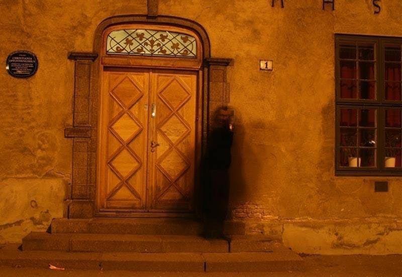 Kongens gate 1, bygning fra 1600-tallet, med en flott utsmykket dør - en sort menneskeskikkelse på trappen