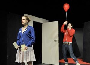 Schauspieler auf der Bühne mit rotem Luftballon