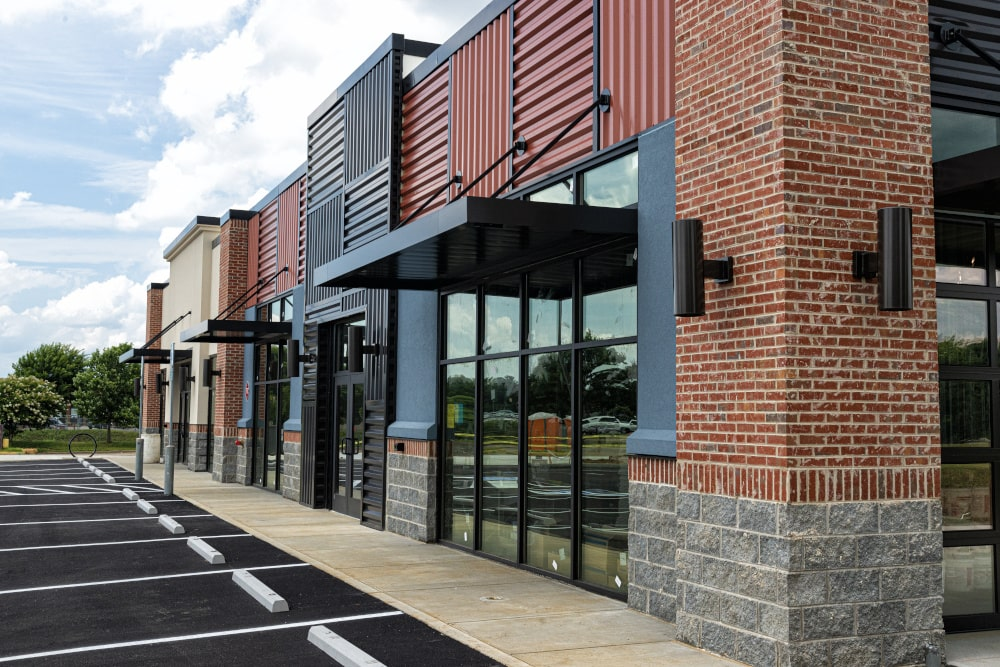 Modern retail building exterior, with brick pillars and metal accents.