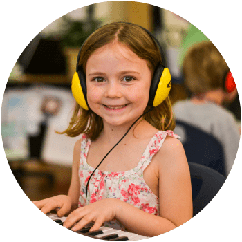 Girl learning to play the piano in group piano lessons after-school or online