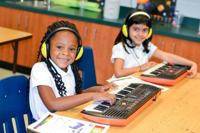 Young girl learning piano in group lessons after-school or online