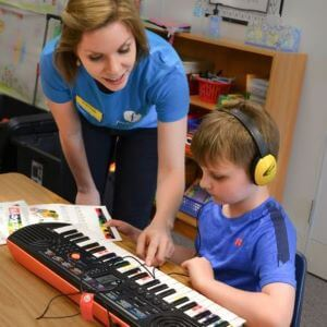 Piano teacher helping young student find notes