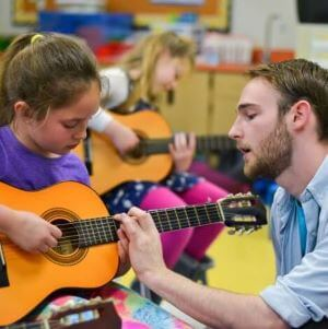 Guitar teacher helping student in group lessons