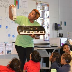 Piano teacher showing note names in group lessons