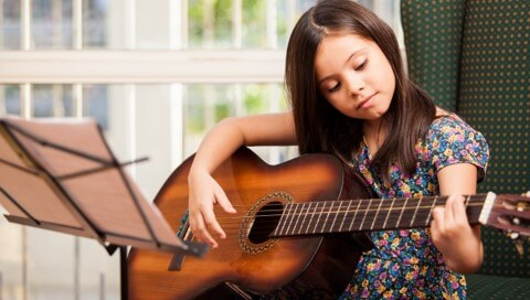 young girl guitar student learning chords