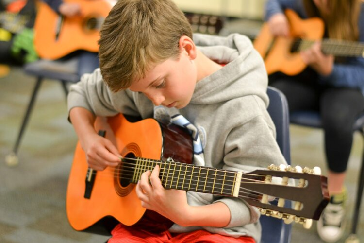 young boy guitar student tuning his guitar