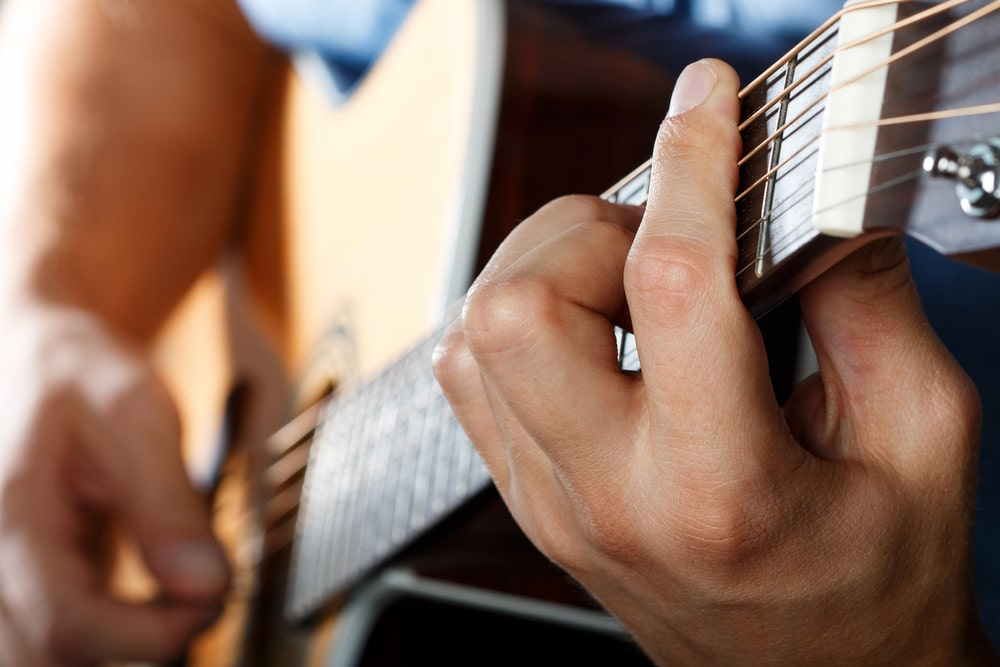 guitar student learning barre chords