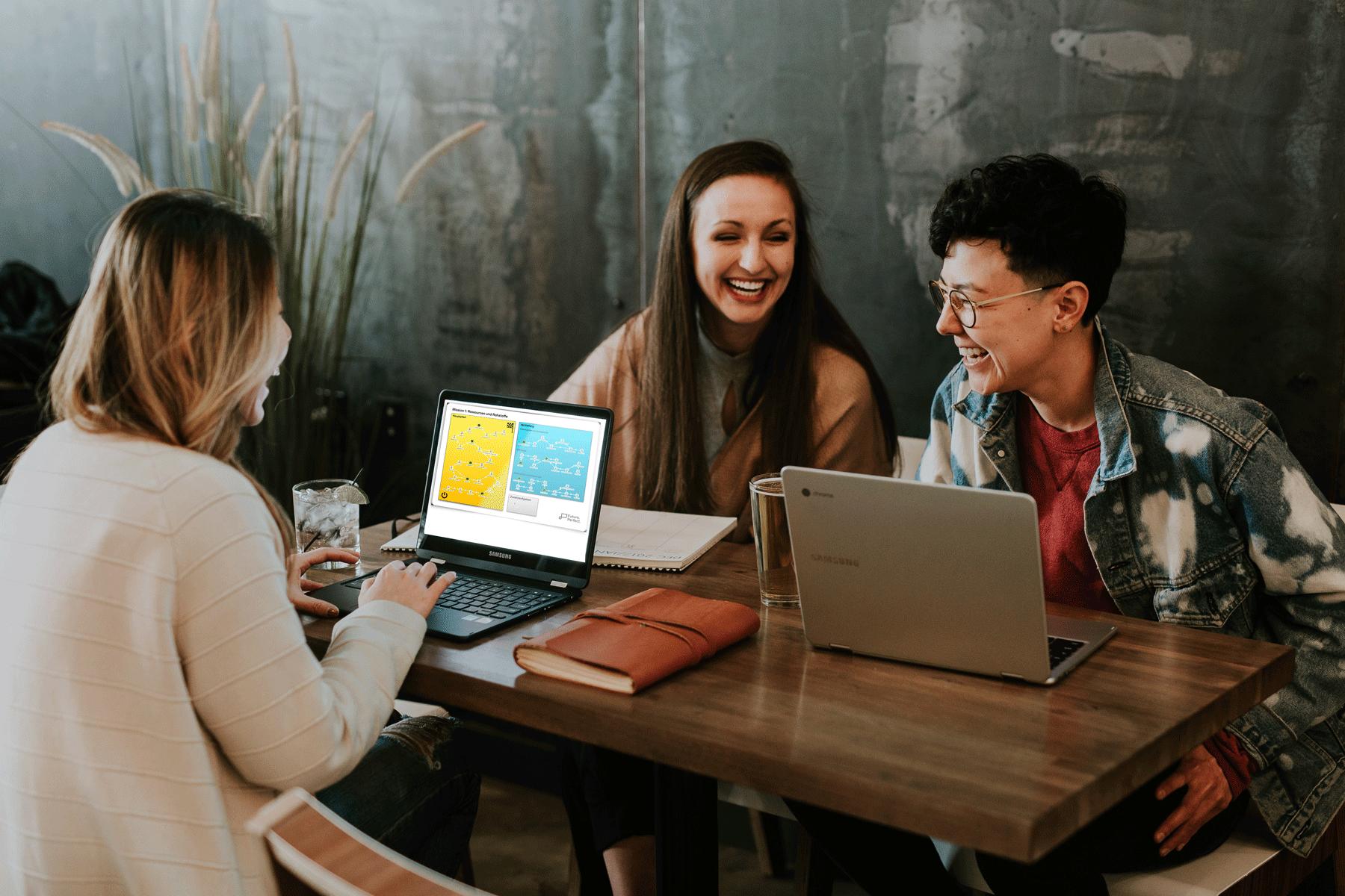 Drei junge Frauen sitzen an einem Tisch und lachen. Auf dem Bildschirm eines Laptops sieht man, dass sie mit Future Perfect lernen.