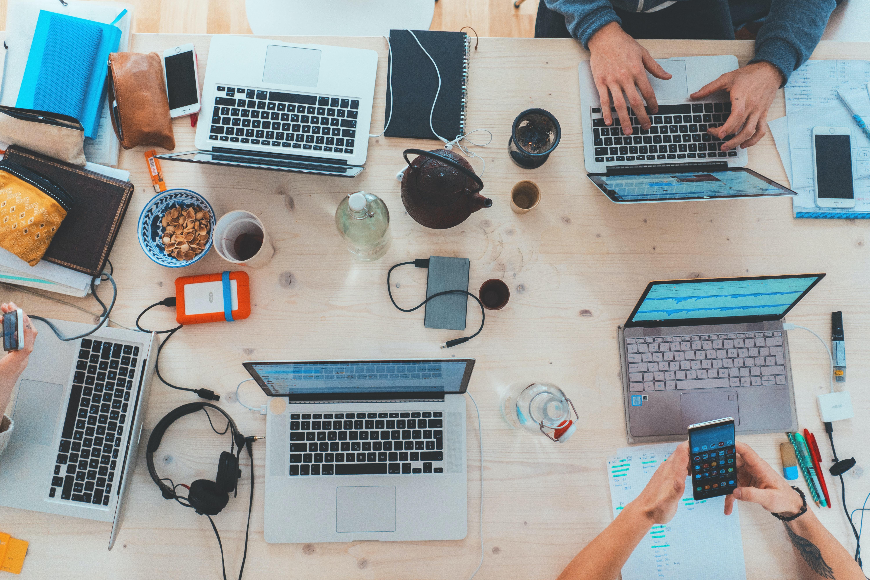 Zahlreiche Laptops und elektronische Geräte sind auf einem Tisch verstreut.