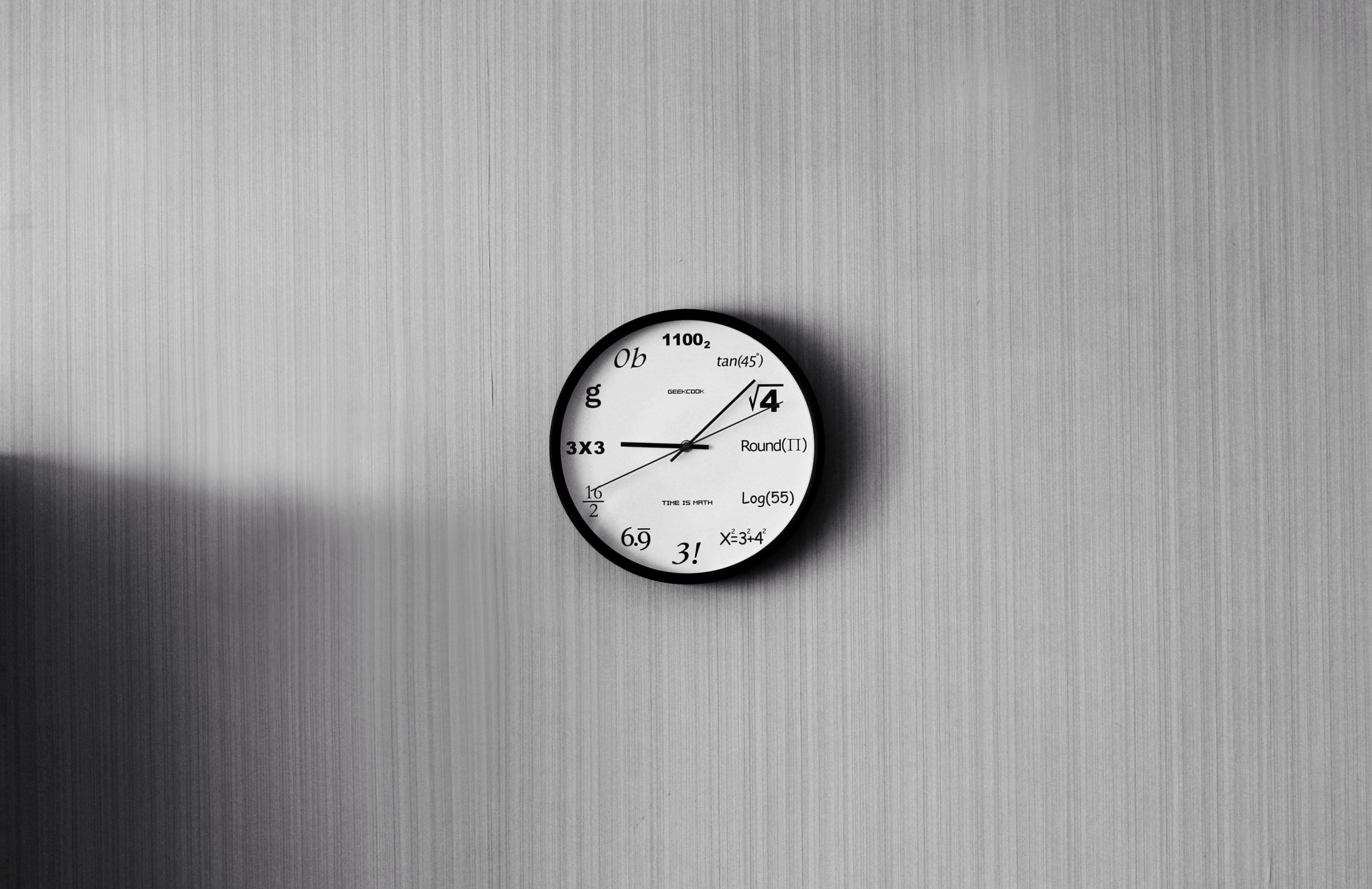 Eine Uhr an einer grauen Wand.