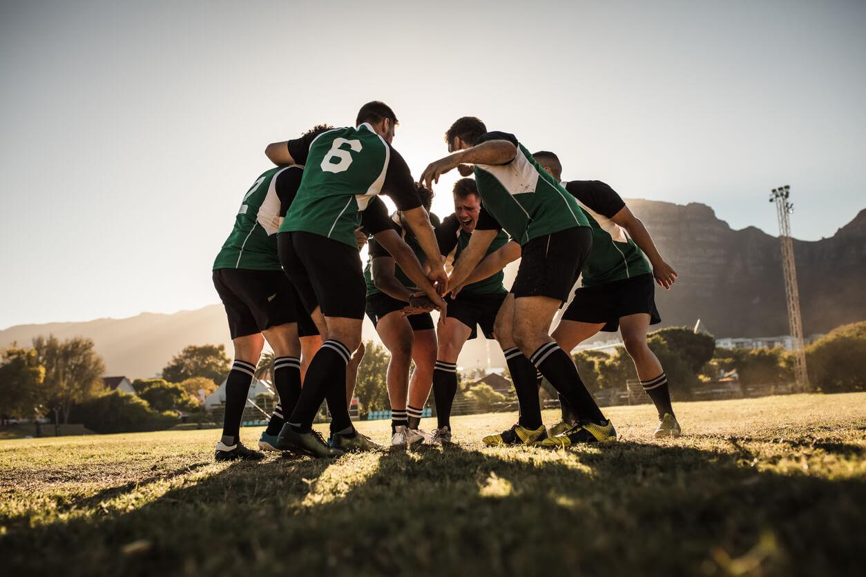 A football team huddling together