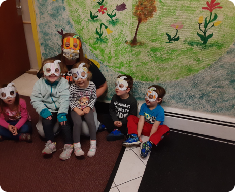 students and a supervisor wearing handmade masks in a child care room
