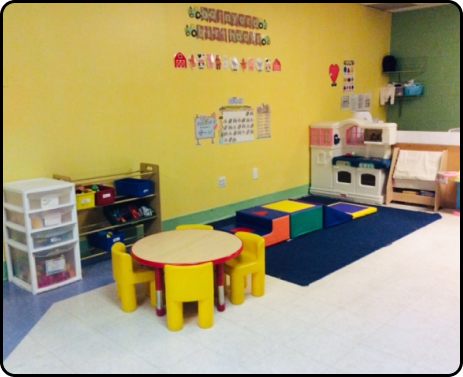 A child care room with a small table and play area