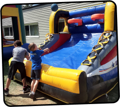 Kids playing inflatable  basketball next to a bounce house
