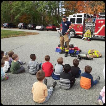 Kids sitting watching a firefighter explain their uniform