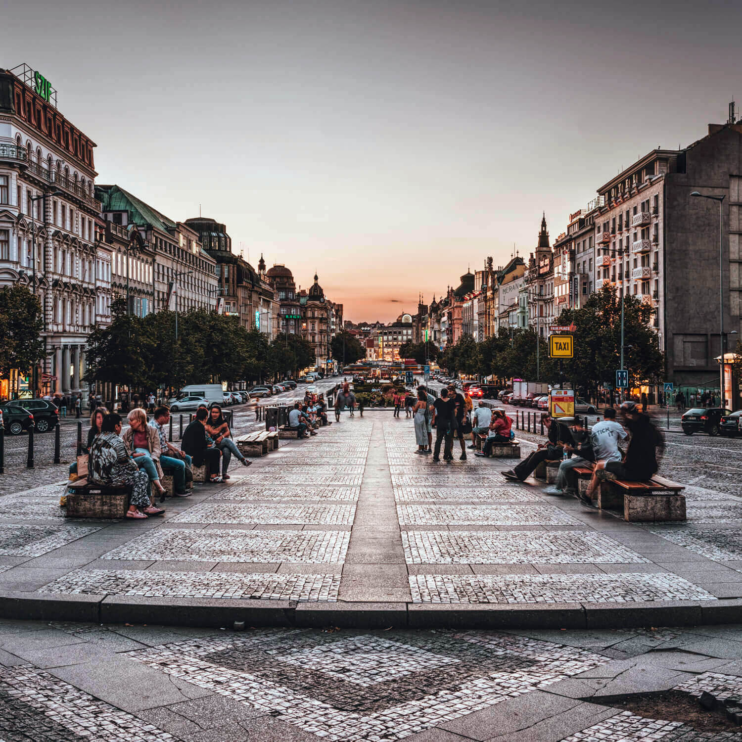 Photo of a city square full of people sitting on benches