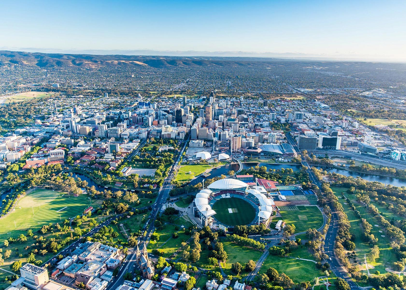Aerial view of Adelaide looking down over the river torrens across the CBD and suburbs all the way to the hills. Parklands and trees feature as a vibrant green.