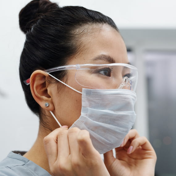 A doctor puts on her mask