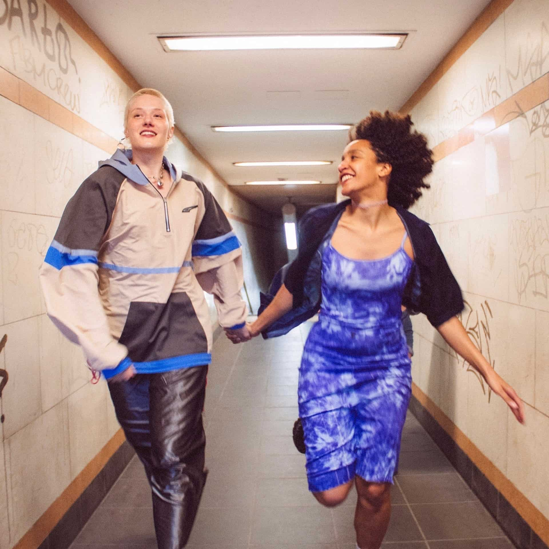 Two people hold hands and run down a hallway, grinning