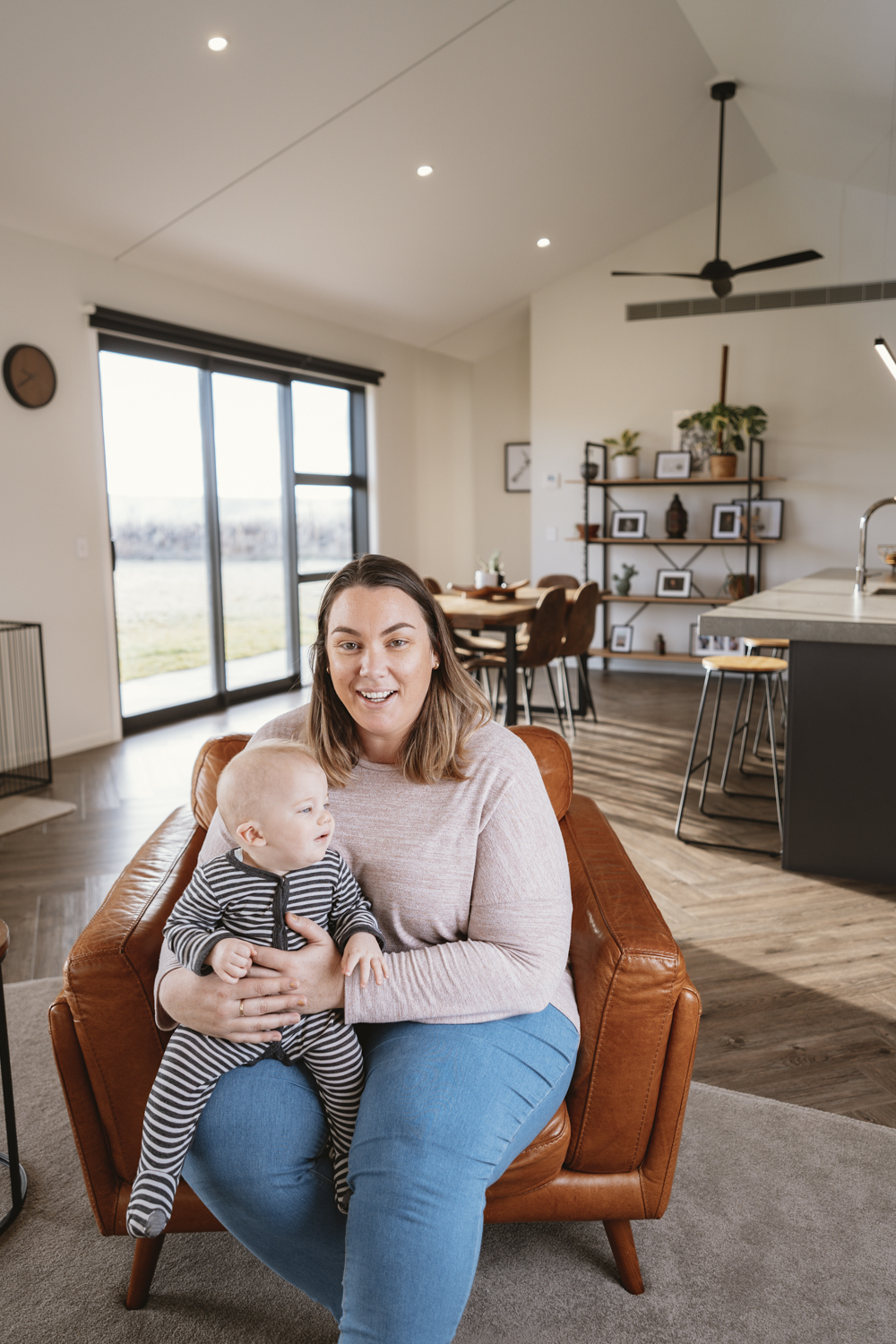 A lady and her baby sit happy in their home