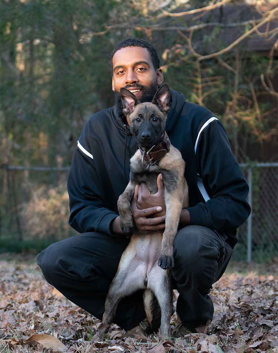 Terry Adams, dog trainer, holding a puppy for a headshot photo