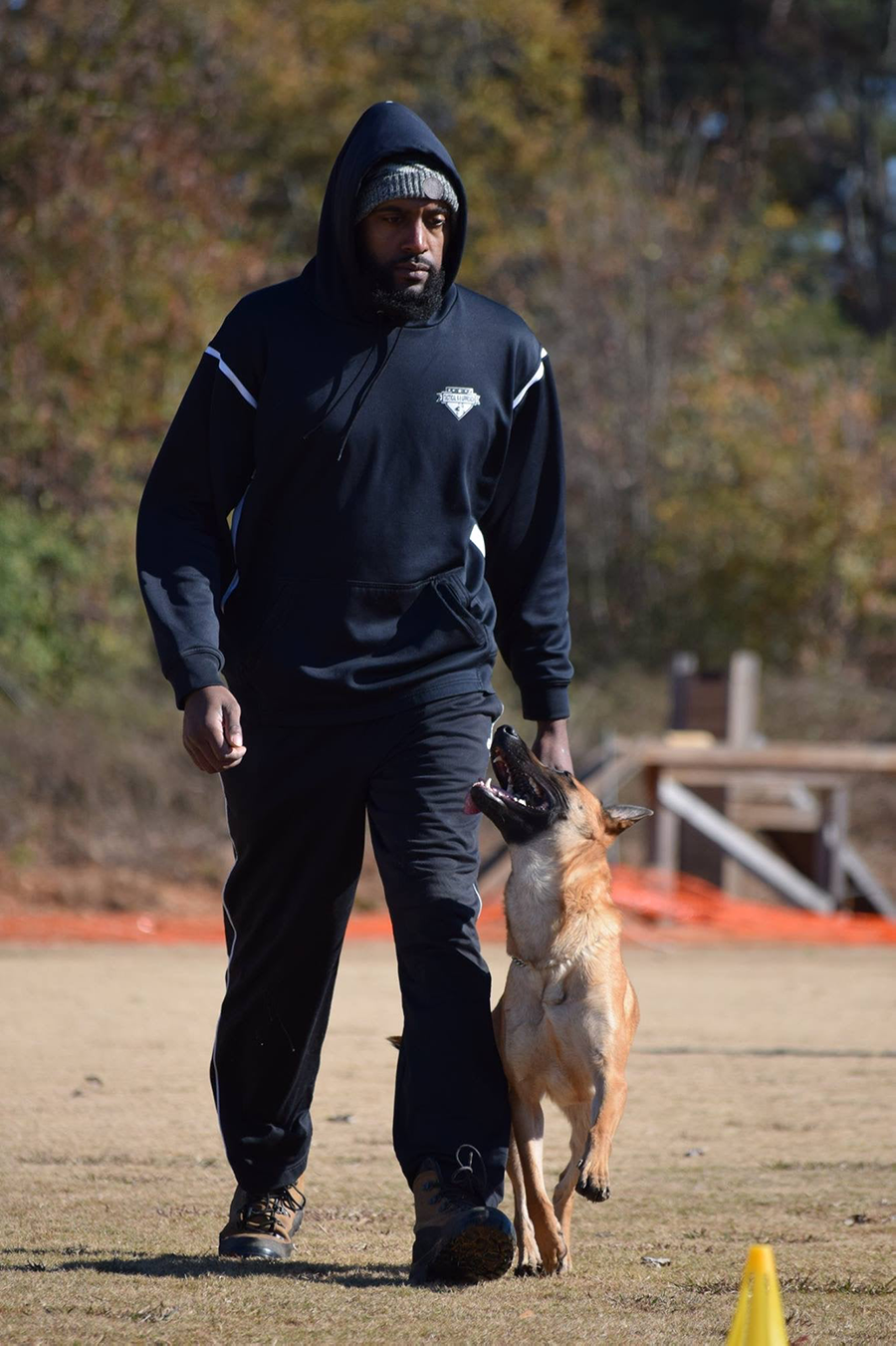 Terry Adams, owner of Tactical K9, walking with a dog during a training session outside.