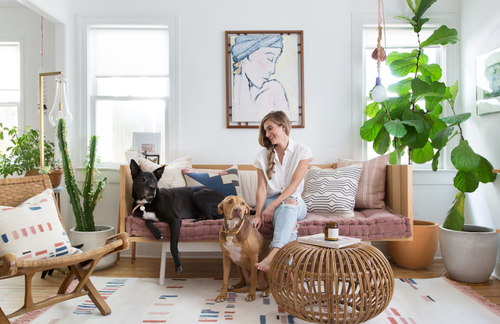 Interior designer Claire Zinnecker sits with her two dogs in an interior she designed for Lulu & Georgia.