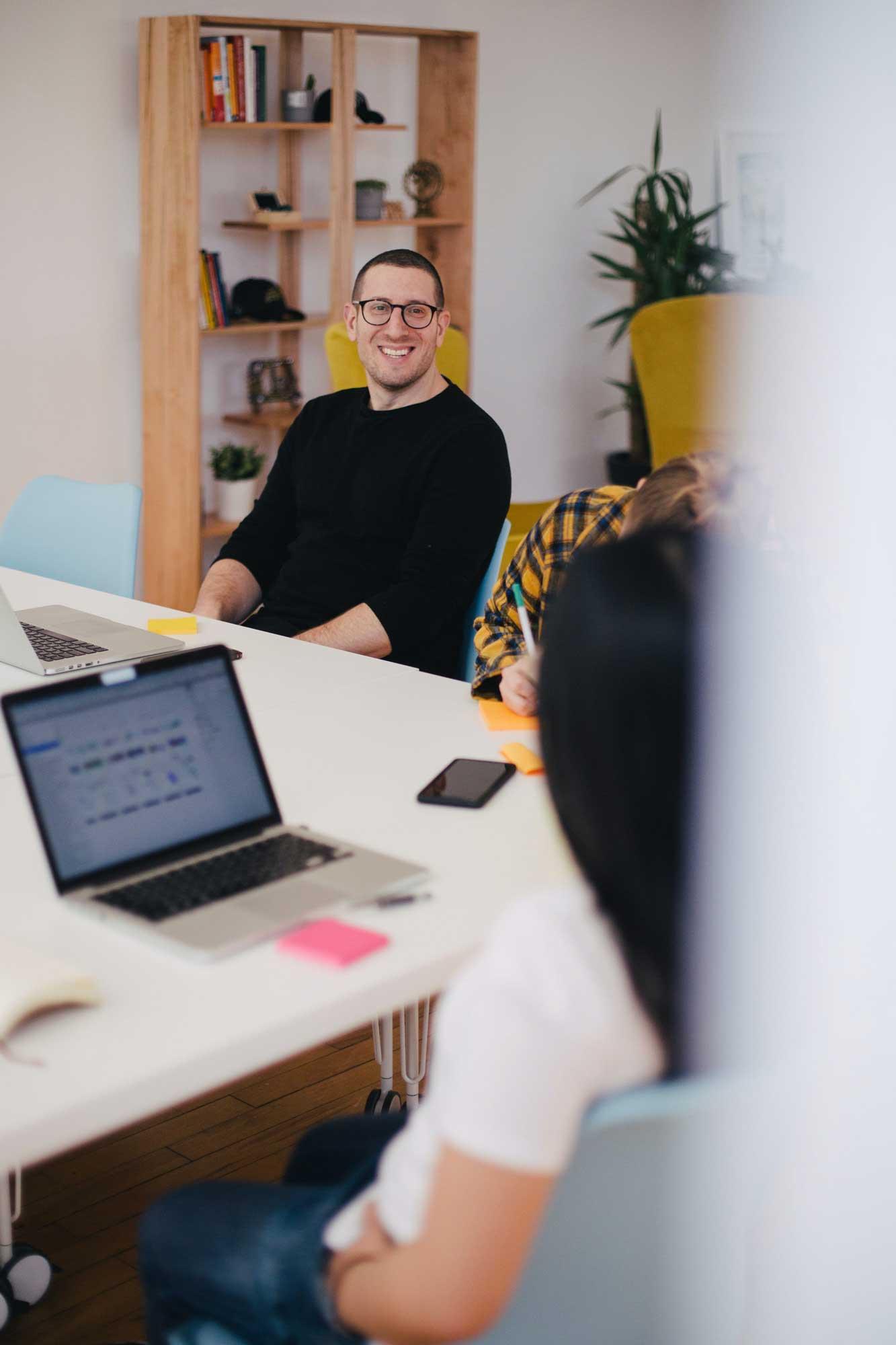 Drei Mitarbeiter einer Internetagentur sitzen am Meetingtisch