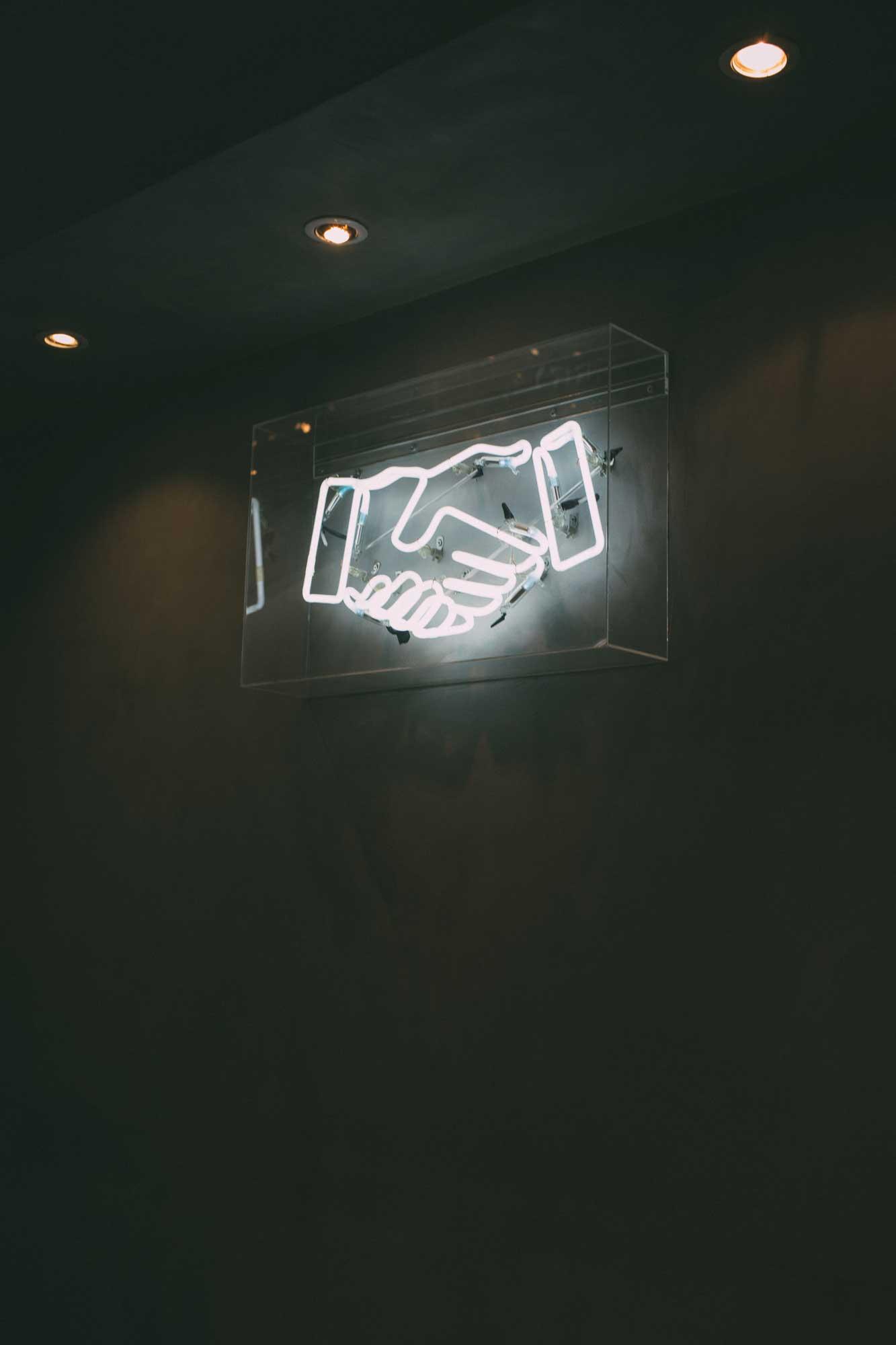 Lichtinstallation mit zwei Händen im Handschlag