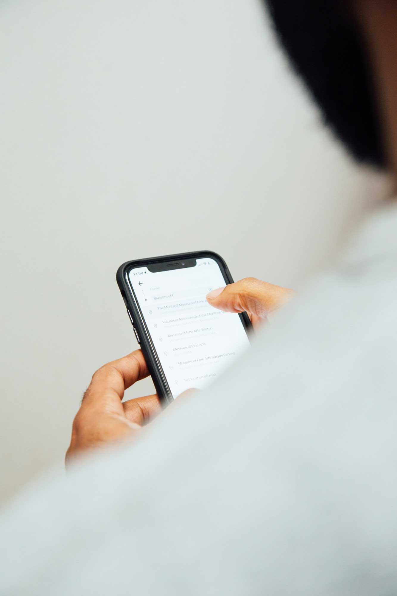 Person tippt mit rechtem Daumen auf das Display eines Smartphones