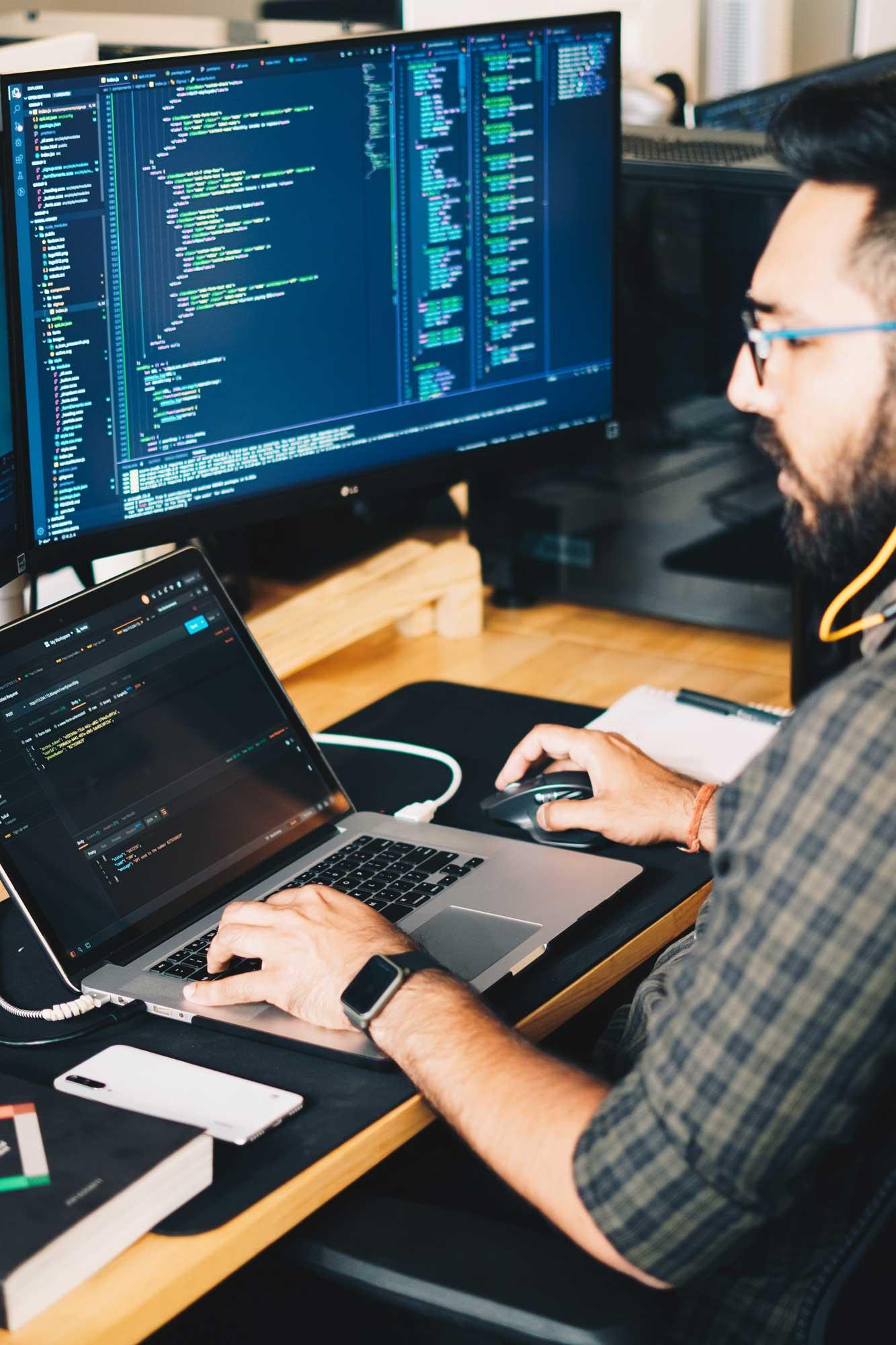 Mann sitzt an einem Schreibtisch in einer Marketing Agentur und programmiert am Laptop
