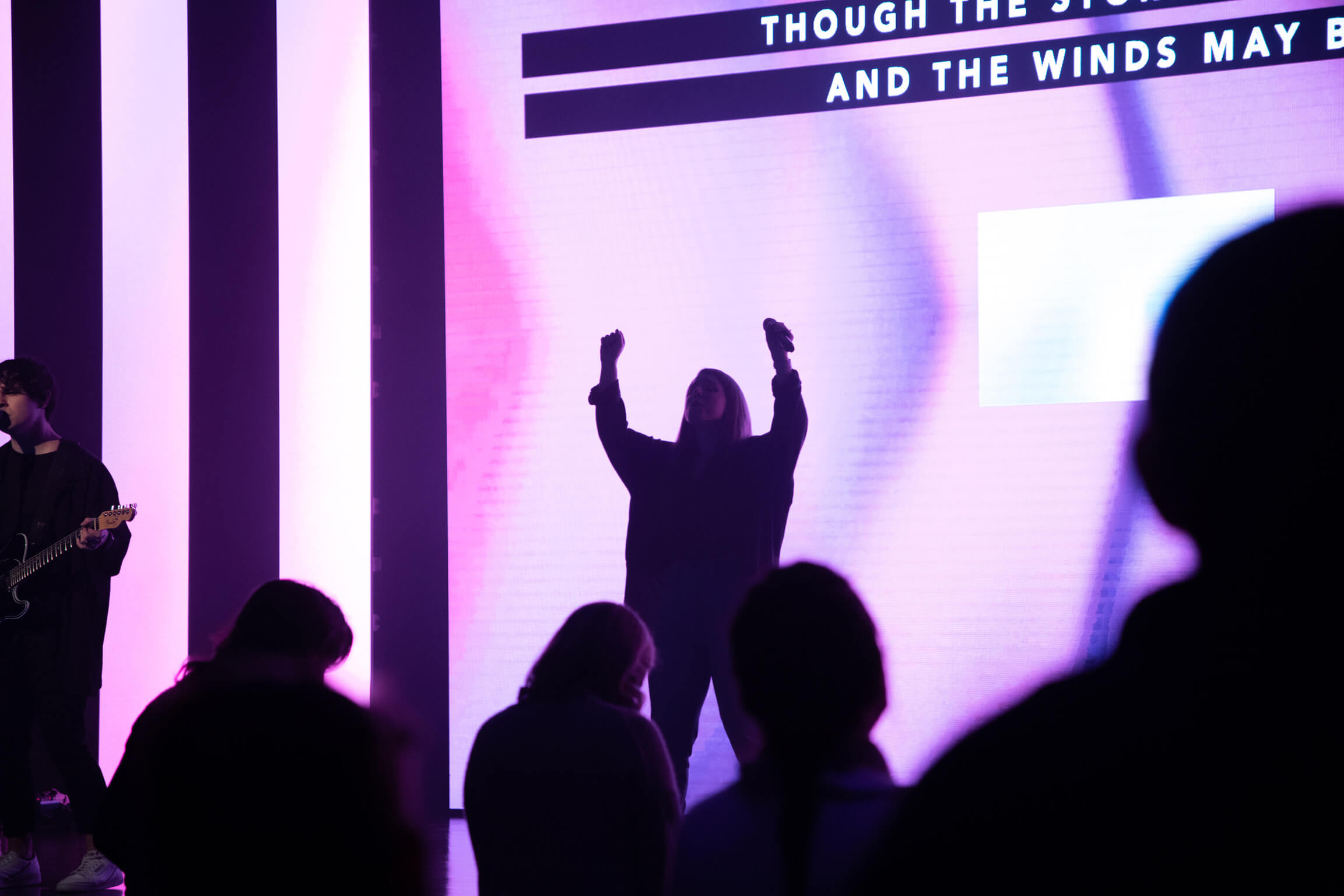 A worship leader with both arms raised on stage.