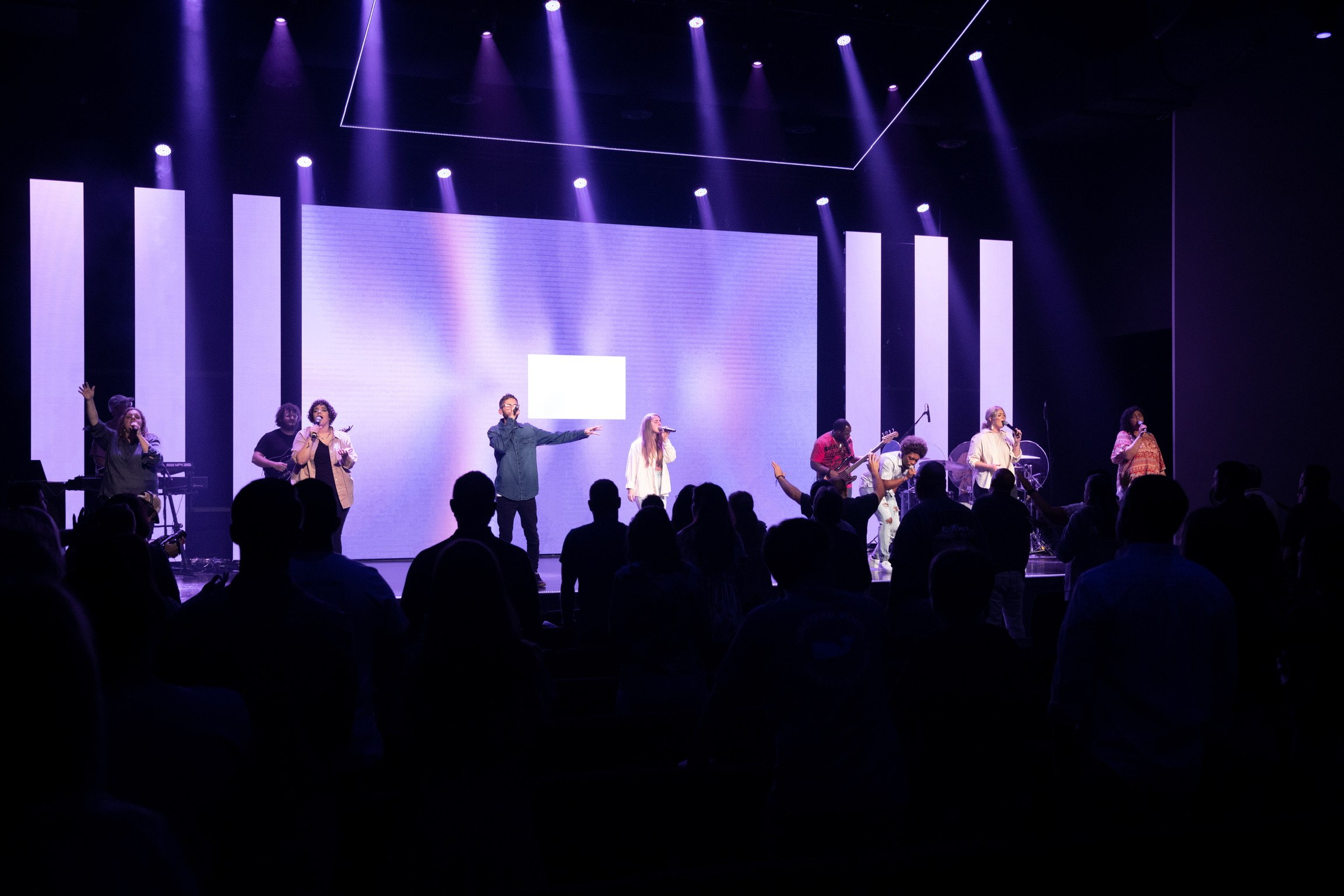 LIFE CO. church auditorium full of people singing and worshipping with a band on stage
