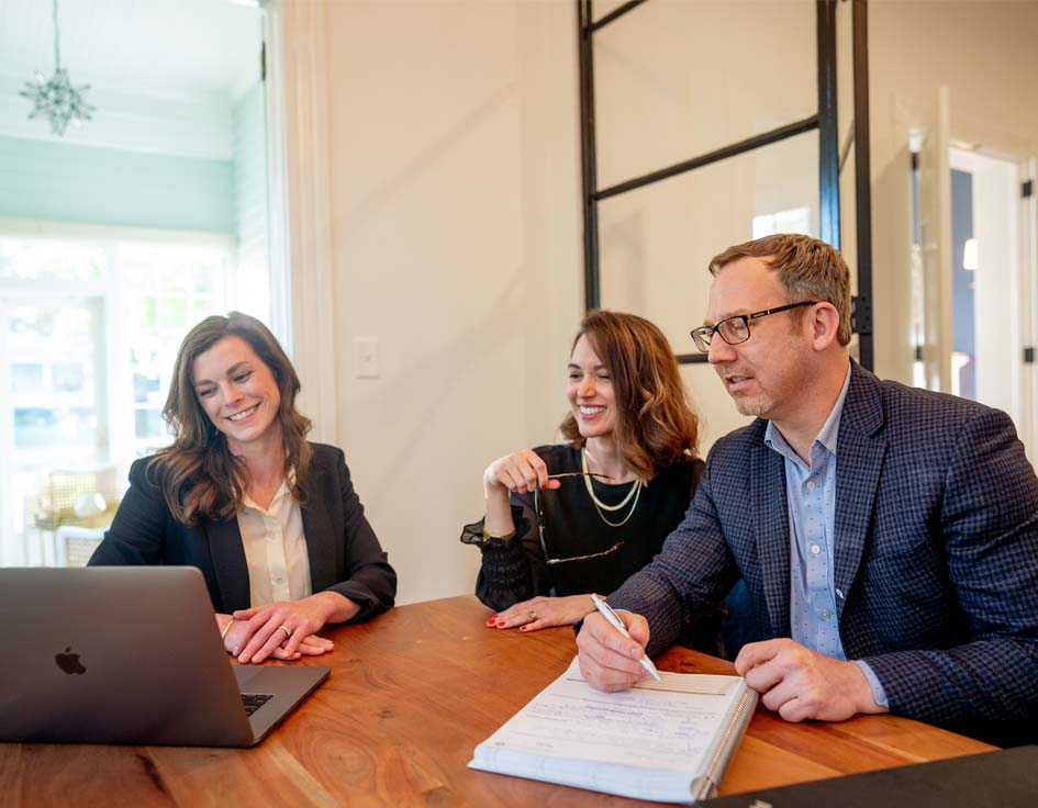 Three financial planners working together around a desk, image