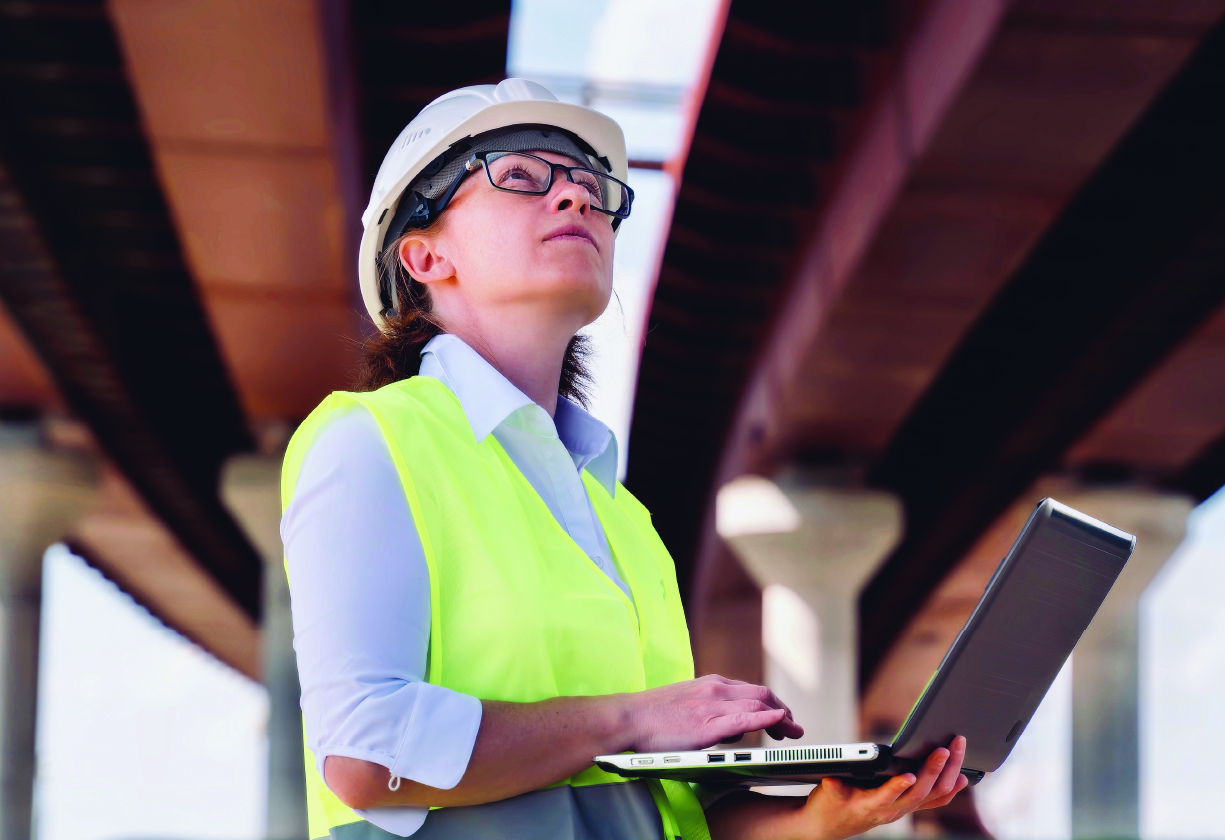A woman in construction inspecting a bridge with a laptop