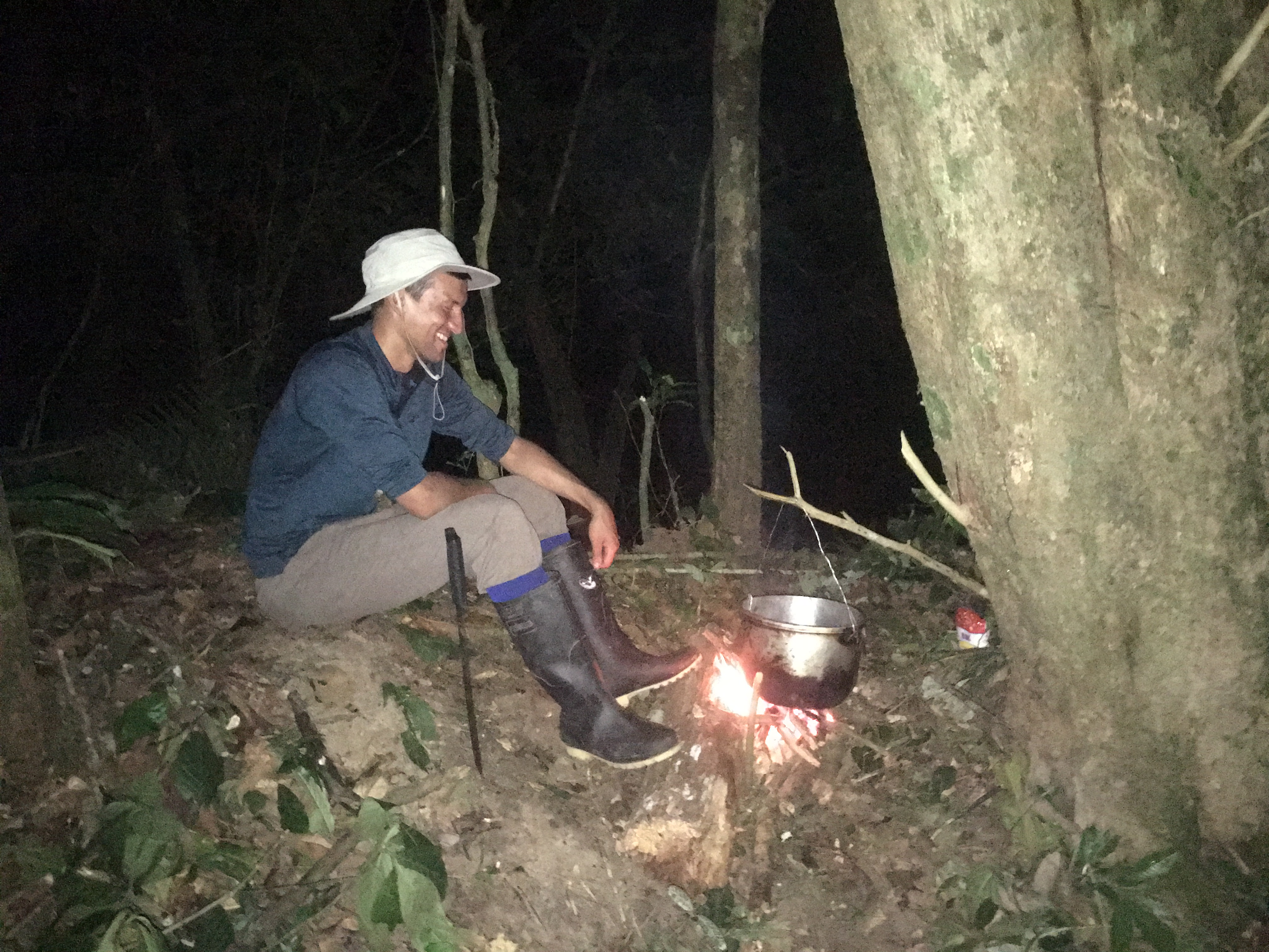 Image of AJ tending to a pot in the Amazon forest