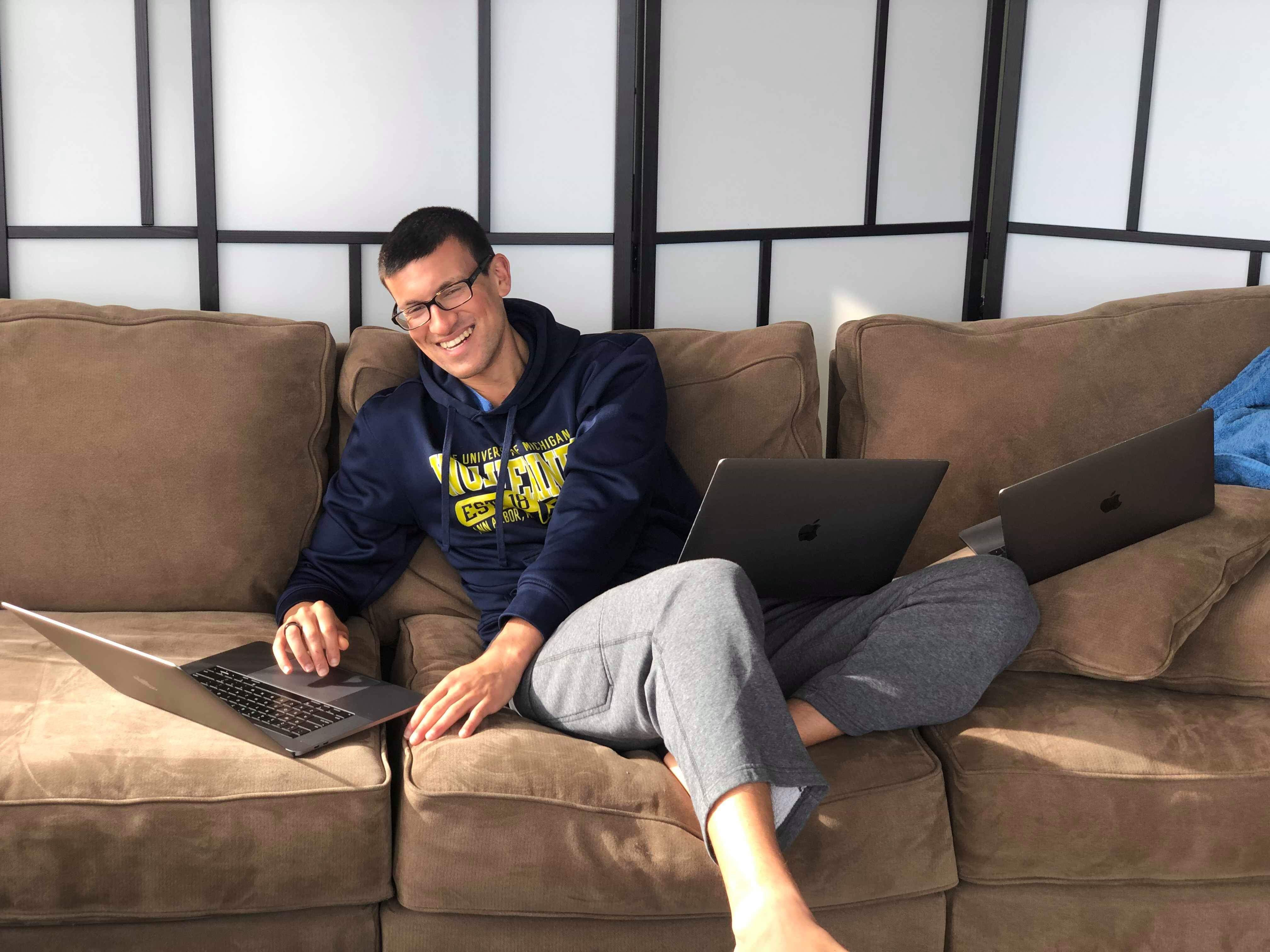 Image of AJ with 3 laptops working on Conscious Insights