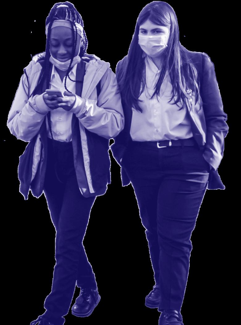 Two schoolgirls walking, one is on their phone