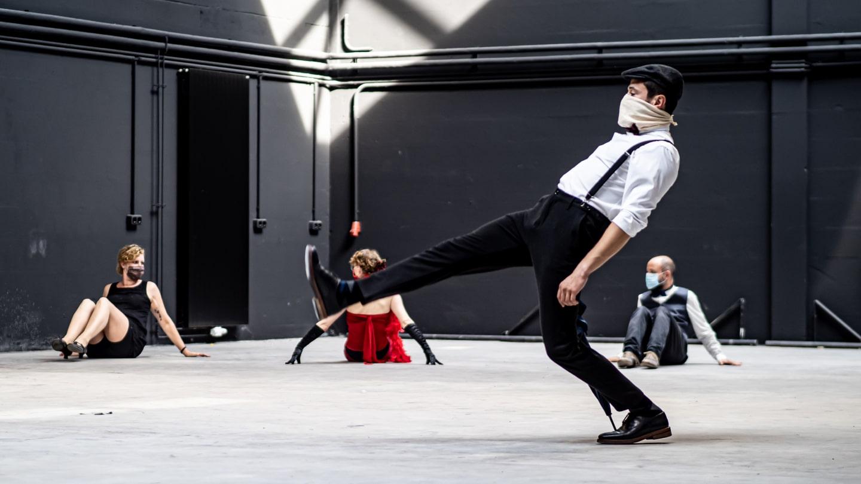 Tanzaufführung, Mann läuft mit steifem erhobenen Bein von rechts nach links
