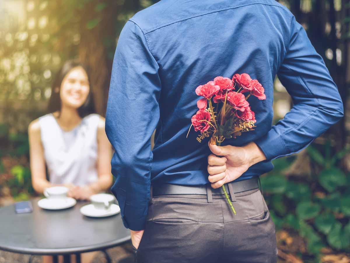 Mann versteckt Blumen hinter dem Rücken Frau sitzt im Hintergrund