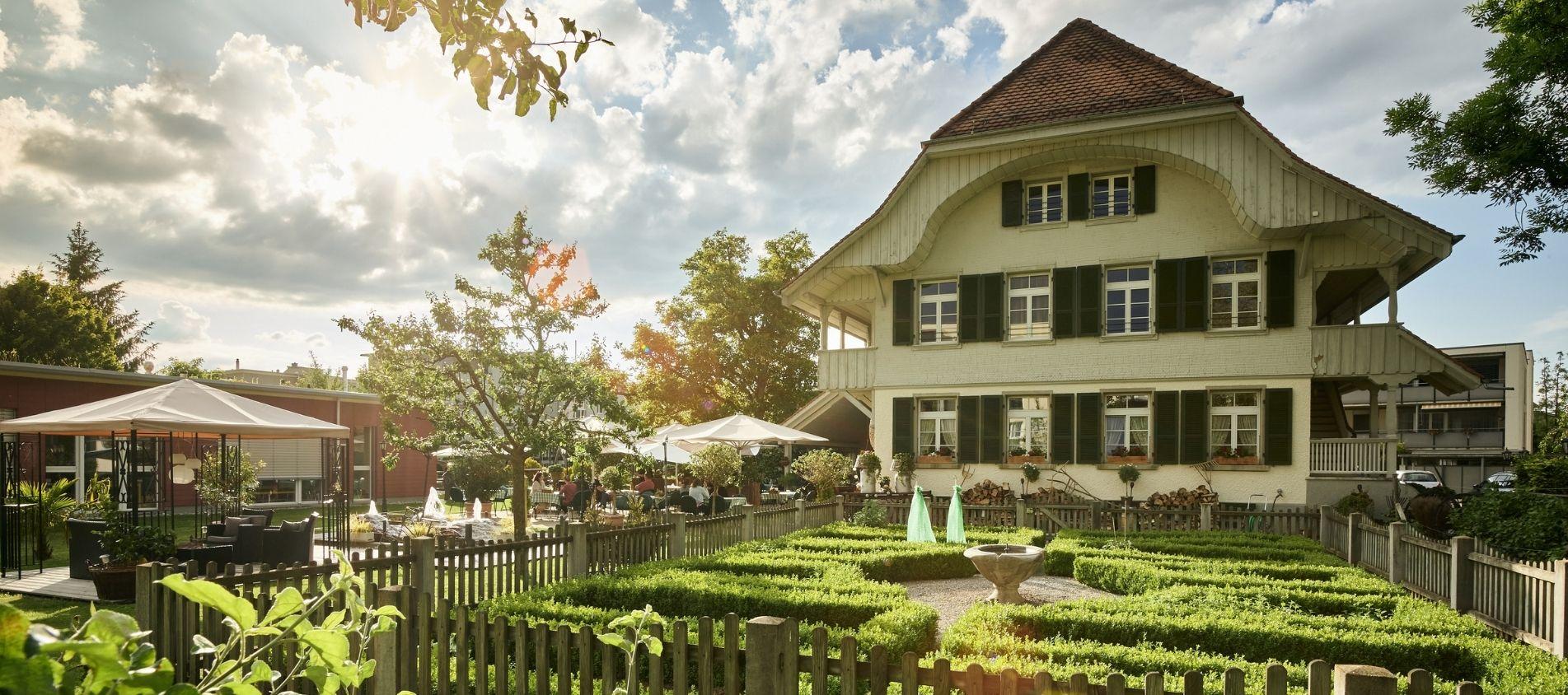 Bauernhaus von aussen mit Garten und Baum vorne dran